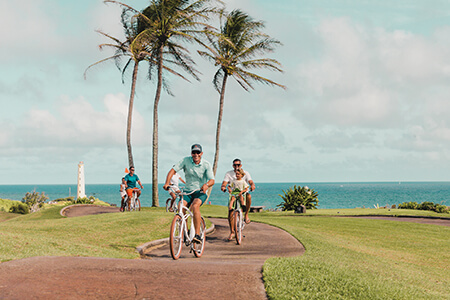 family riding bikes near oceanfront in Kauai.