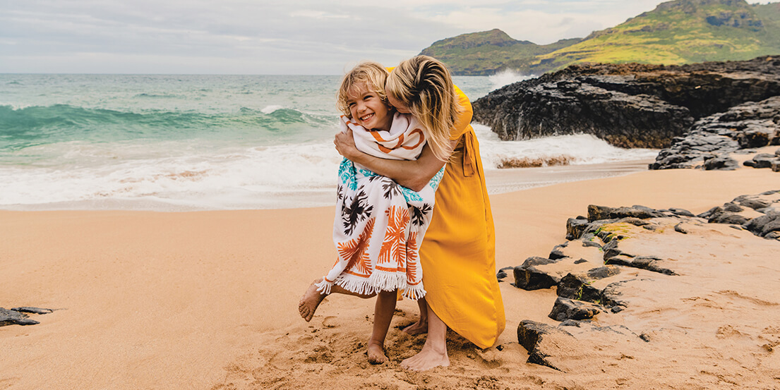 mother and daughter hugging on beach in Kauai