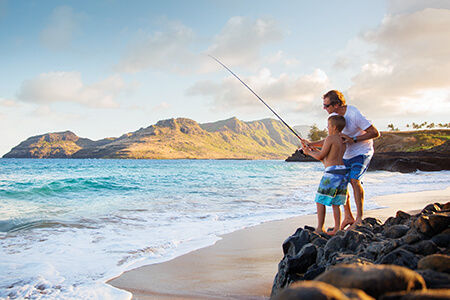Father and son fishing on beach in Kauai.
