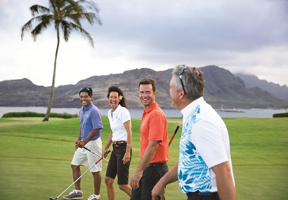 Friends golfing near ocean in Kauai.