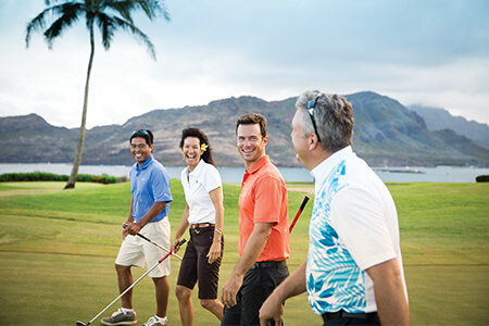 Friends golfing near oceanfront in Kauai.